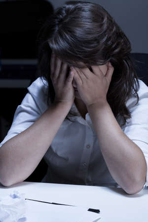 glum: Glum woman in office going to cry Stock Photo