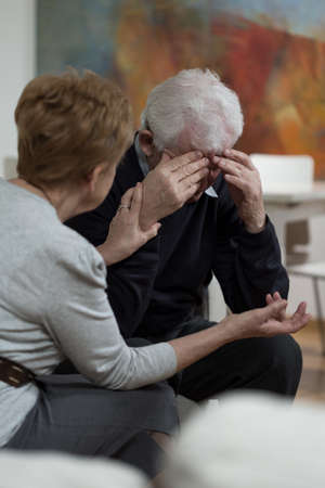 trouble: Elder woman supporting her sad senior husband
