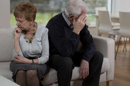 pareja enojada: Ofendido pareja anciano sentado en el sofá