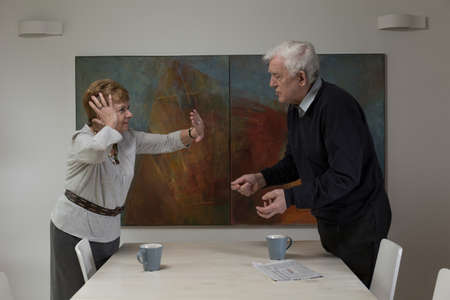 Aged couple during argument at the table