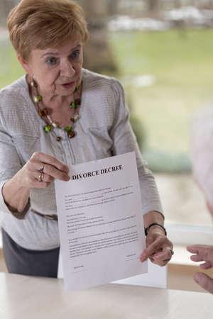 law breaking: Retired woman giving husband divorce decree paper
