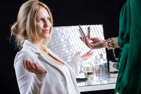beautician: The bride chooses the color of lipstick with beautician