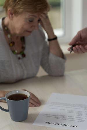 Heartbroken woman going to sign divorce paper Stock Photo