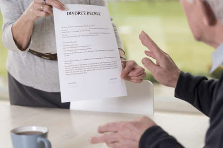 Close-up of female hands holding divorce paper