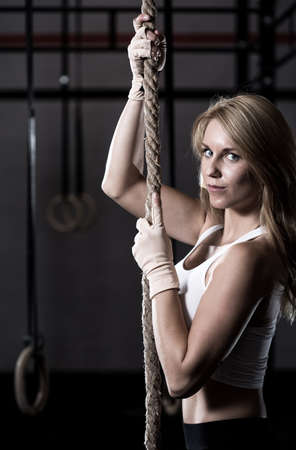 Blonde fit girl during rope climbing exercise photo