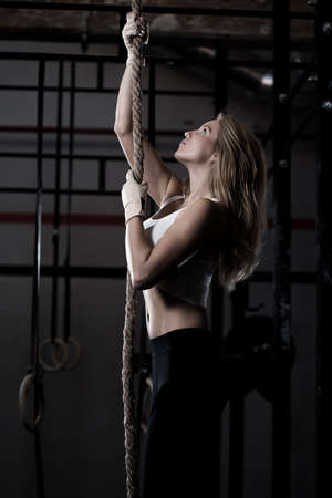 ropes: Crossfit training - fitness woman during rope climbing Stock Photo