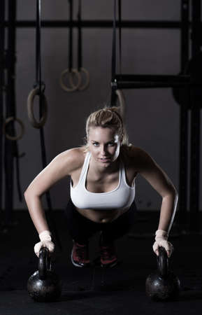 vida sana: Mujer apta que hace empuje hacia arriba con pesas Foto de archivo