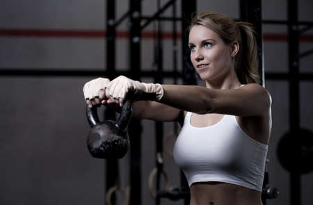 exercise room: Young beautiful woman exercising with kettlebell