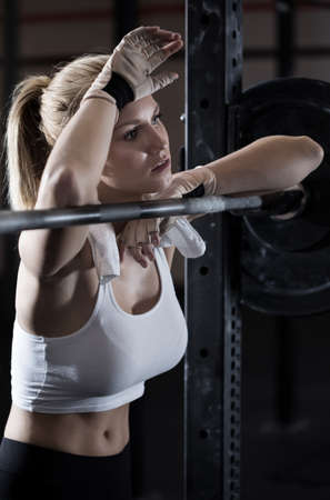 tired: Young pretty girl tired after weightlifting at gym Stock Photo