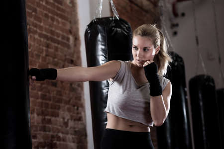 girl kick: Horizontal view of girl training kick boxing