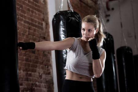 patada: Vista horizontal de la chica saque entrenamiento de boxeo
