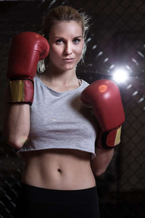 hands out: Vertical view of woman wearing boxing gloves