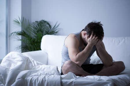 persona deprimida: Hombre joven con la depresi�n sentado en la cama Foto de archivo