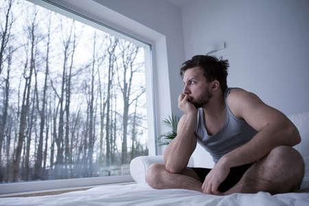 sleeplessness: L'uomo soffre di insonnia mordendosi le unghie Archivio Fotografico