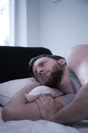 get tired: Image of awake man lying in bed
