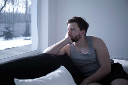 depressed man: Man suffering from insomnia waking up early