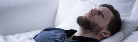 sleeplessness: L'uomo soffre di insonnia sdraiato con gli occhi aperti