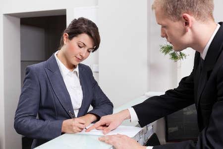 ドキュメントに署名する魅力的な実業家の水平方向のビュー