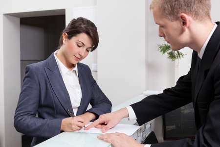 Horizontal view of attractive businesswoman signing document Stock Photo