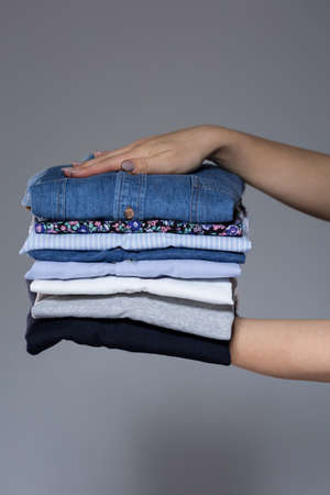 Woman holding stack of clothes in her hands at home photo