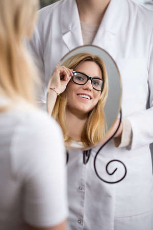 shortsightedness: Woman testing new eyeglasses by looking at the mirror