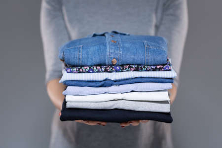 moda ropa: Mujer que sostiene la ropa doblada en las manos