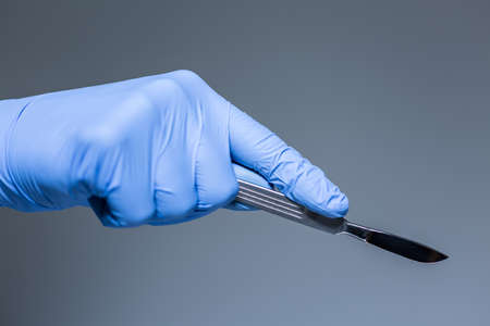 Close-up of scalpel in the hand in glove of doctor Archivio Fotografico