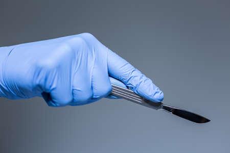surgical: Primer plano de bisturí en la mano en el guante de médico