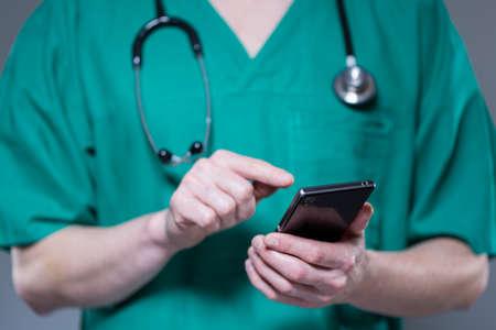Close up de docteur en uniforme en utilisant téléphone au travail
