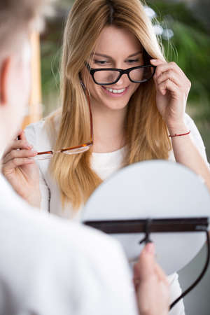 shortsightedness: Vertical view of woman choosing new glasses