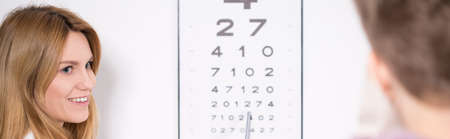 shortsightedness: Optician using Snellen test during eye examination