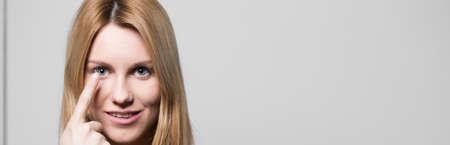 lentes de contacto: Mujer atractiva con el defecto del ojo usando lentes de contacto