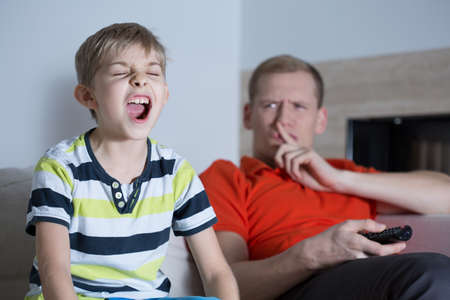 annoy: Little screaming son and his annoyed young father