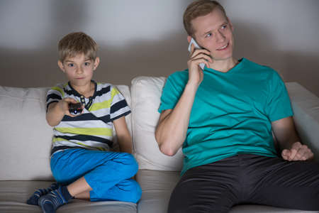 the color of silence: Young father talking the phone during son watching television