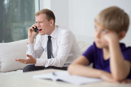irate: Young irate father talking on the phone in family room Stock Photo
