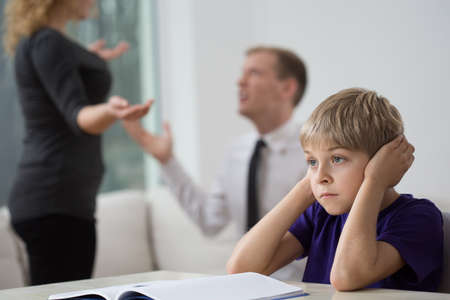 upset: Sad little boy and family fight in living room Stock Photo