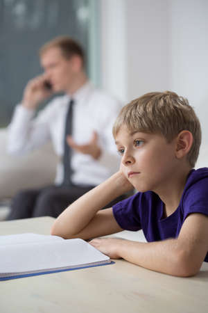 living room boy: Unhappy little boy and dad talking on the phone in the background