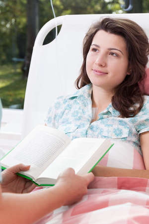 caring nurse: Caring nurse reads a young patient in the hospital Stock Photo