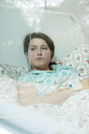 leucemia: Muchacha preocupante con quimioterapia acostado en la cama Foto de archivo