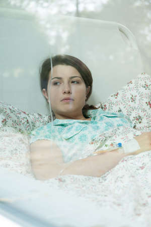 chemotherapy: Worried girl with chemotherapy lying on bed Stock Photo
