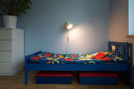 children room: Children small bed with colorful cartoon sheet