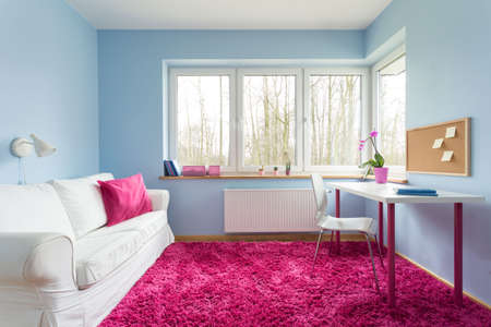 モダンな客室にはブルーの壁とピンクの柔らかいカーペット 写真素材