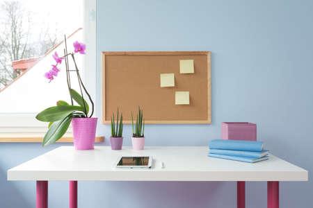 pizarra: Tarjeta del corcho encima de la mesa blanca en sala de estudio de la muchacha linda Foto de archivo