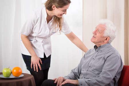 Afbeelding van jonge verpleegster zorg over oudere man Stockfoto