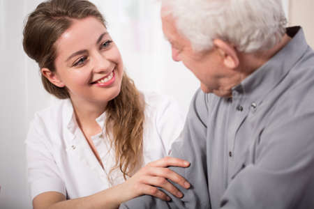 vejez feliz: Imagen de la sonriente enfermera ayudando a hombre mayor