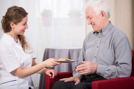social care: Care assistant and retired man at home Stock Photo