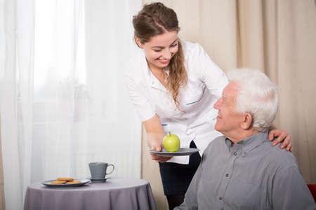 enfermera con paciente: Enfermera útil y pensionista sonriente en su casa Foto de archivo