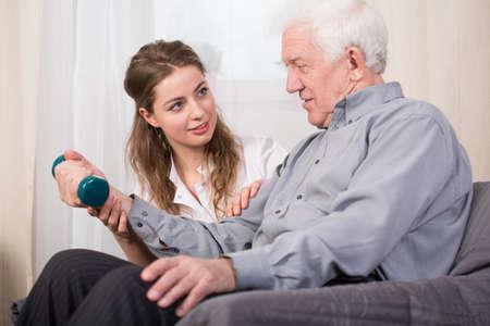fisioterapia: Imagen de la formación del hombre mayor con mancuernas