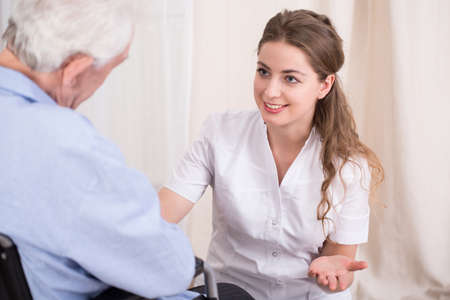 enfermeras: Enfermera hablando con el hombre anciano quedarse en casa residencial