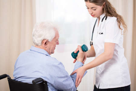 Practitioner showing disabled patient exercise with dumbbell